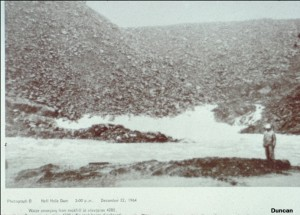 This photo shows the water emerging from the toe of the downstream rockfill shell at 3 PM on December 22, 1964. Some rock has been eroded.