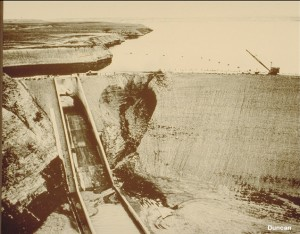 This photo shows the Baldwin Hills Dam after it failed by piping in 1963. The failure occurred when a concentrated leak developed along a crack in the embankment, eroding the embankment fill and forming this crevasse. An alarm was raised about four hours before the failure and thousands of people were evacuated from the area below the dam. The flood that resulted when the dam failed and the reservoir was released caused several millions of dollars in damage.